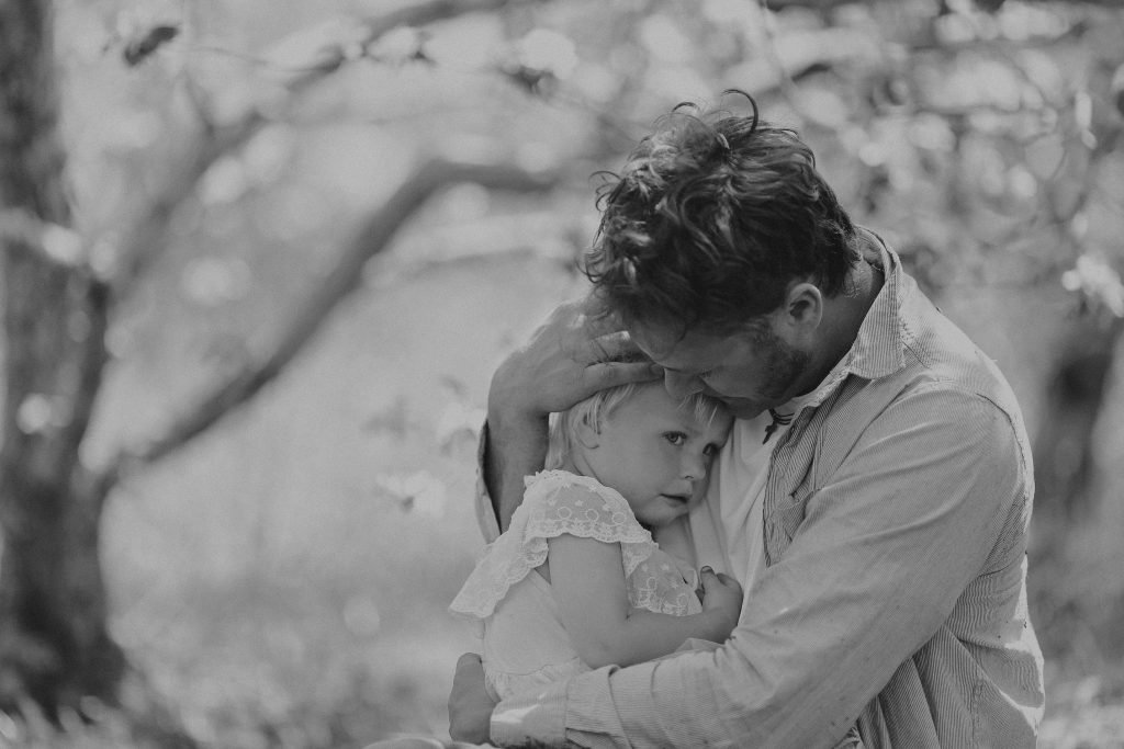 A Good Father is holding and comforting his csad and pouting baby daughter outside on a spring day.